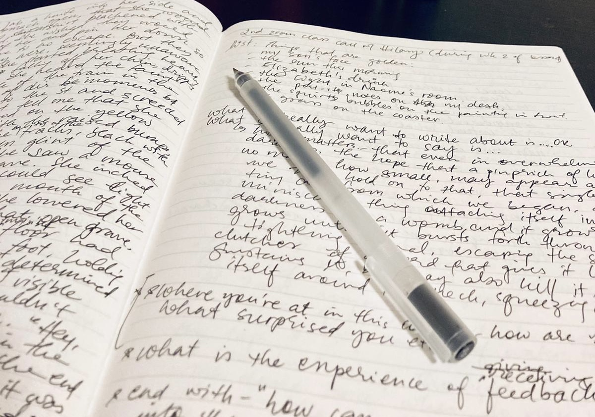 Open notebook with writing in black ink on both pages. An uncapped pen sits across one page.