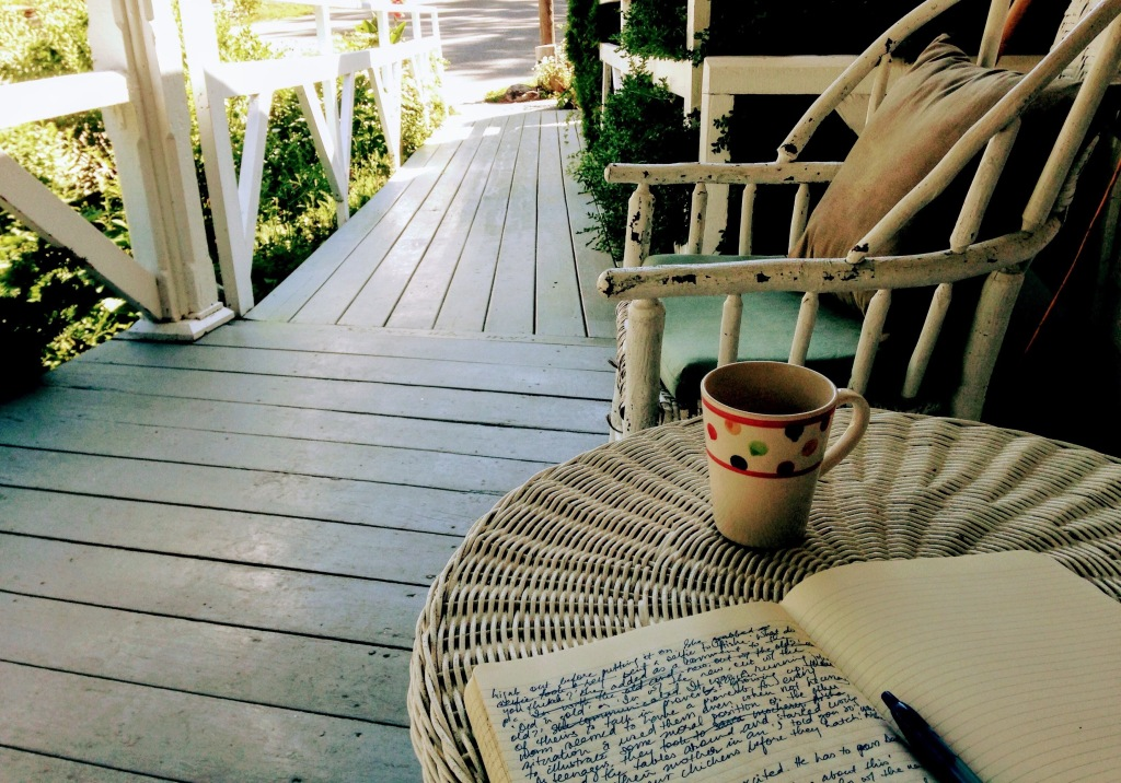A notebook with writing on one page and an empty cup on a round table on a porch outdoors. An empty chair is next to the table and a path leading outside.