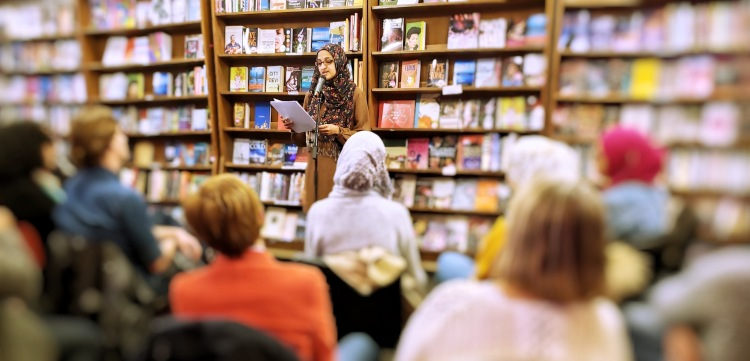 Hajera Khaja is holding some sheets of paper and reading into a mic in front of an audience. Behind her is a wall of books.